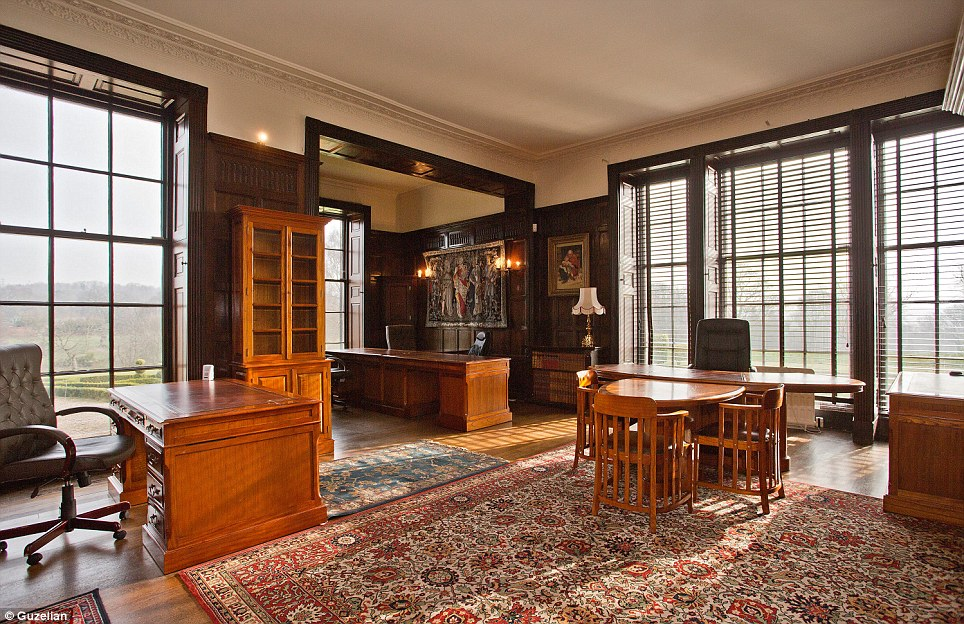 Study: A desk with a large leather chair sits in front or large bay windows. The no-classical drawing room is scattered with artwork and classic lighting