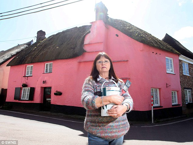 Upset: Ann Kennedy in front of her listed cottage in Devon, which the local council say is too pink